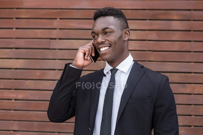 Positivo sorrindo bem sucedido Africano empresário americano falando no telefone móvel ao lado urbano listrado parede de madeira — Fotografia de Stock
