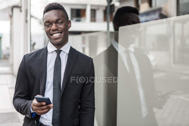 Stylish happy positive smiling black manager in suit looking in camera as using cellphone while leaning on glass window — Stock Photo