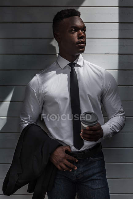 Pensive tired black businessman standing in shade with coffee to go and suit jacket on gray striped wall and looking away — Stock Photo