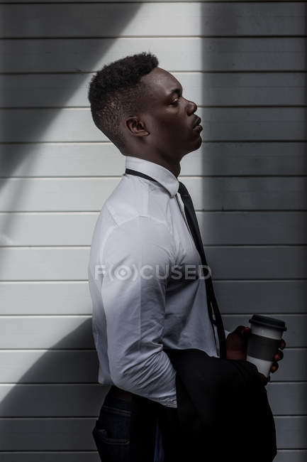 Side view of pensive black businessman standing in shade with coffee to go and suit jacket — стокове фото
