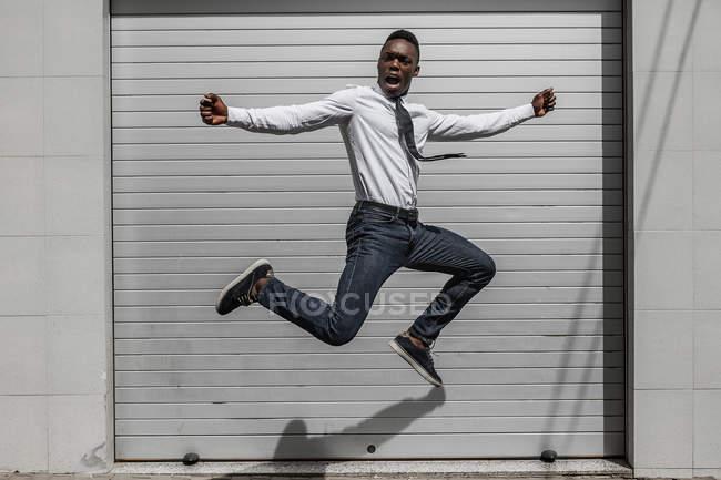 Захоплений афроамериканський крик бізнесмен стрибає за святкування успіху біля сірої смугастої стіни. — стокове фото