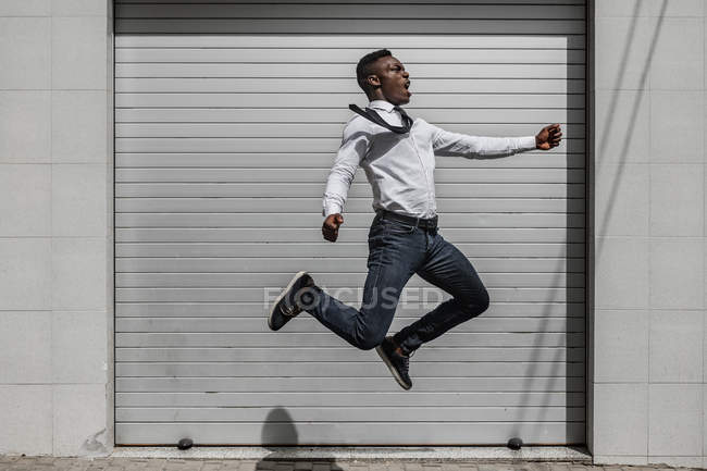 Excited African American screaming businessman jumping for celebrating success beside street gray striped wall — Photo de stock
