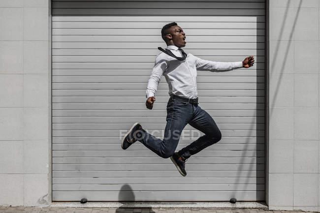 Excite Africano americano gritando empresário pulando para comemorar o sucesso ao lado de rua cinza parede listrada — Fotografia de Stock