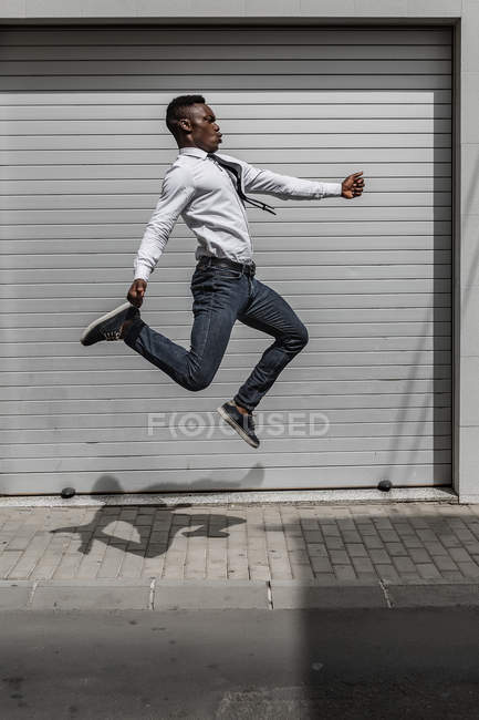 Excited African American businessman jumping for celebrating success beside street gray striped wall — Stock Photo