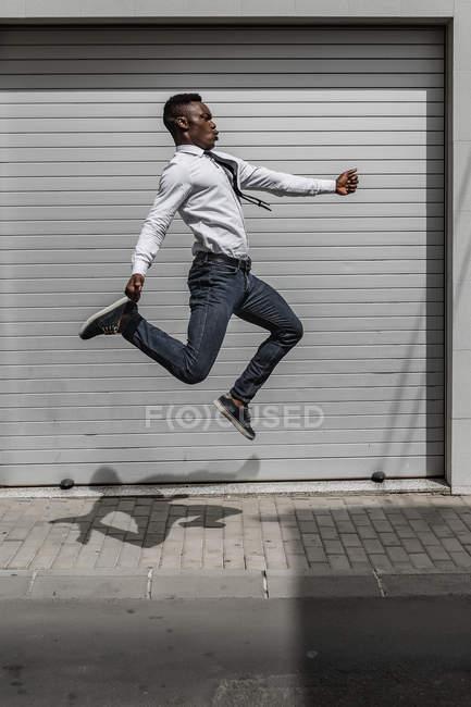Homme d'affaires afro-américain excité sautant pour célébrer le succès à côté du mur rayé gris rue — Photo de stock