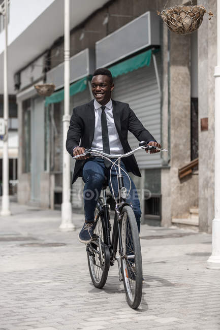 African American positive stylish entrepreneur in suit bicycling to work on urban sidewalk in city — Stock Photo