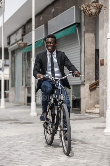 African American entrepreneur élégant positif en costume vélo pour travailler sur le trottoir urbain en ville — Photo de stock