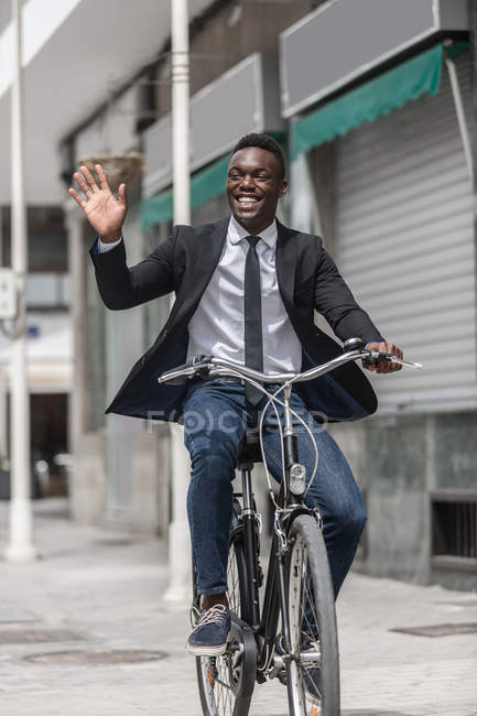 African American positive entrepreneur in suit bicycling to work on urban sidewalk and greeting as waving hand — Stock Photo