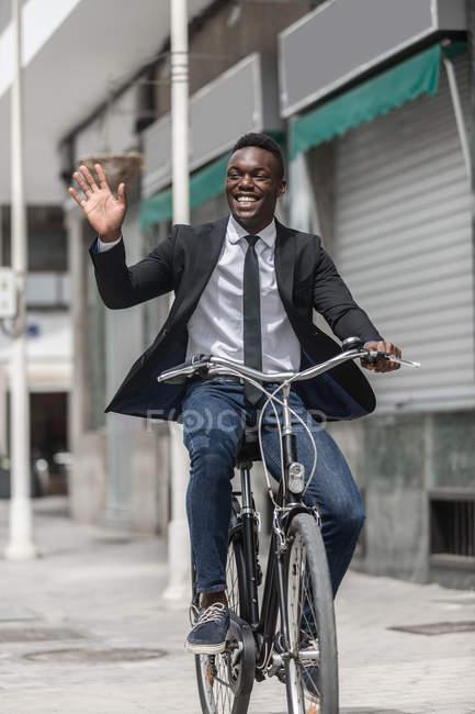 Afro-americano imprenditore positivo in tuta cicloturismo per lavorare sul marciapiede urbano e saluto come mano che saluta — Foto stock