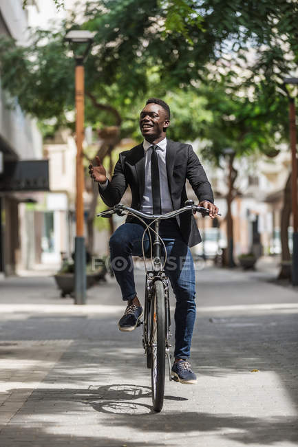 African American positive stylish entrepreneur in suit bicycling to work on urban sidewalk in city — Photo de stock