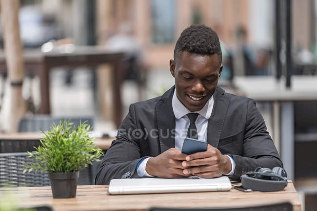 Black businessman using cellphone as sitting in bar — Stock Photo