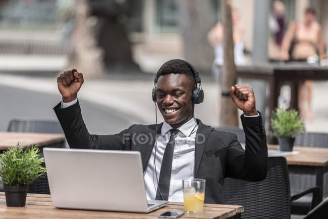 Joyeux homme noir joyeux en costume se réjouissant du succès avec les mains levées assis dans le café à l'extérieur avec ordinateur portable et écouteurs filaires — Photo de stock