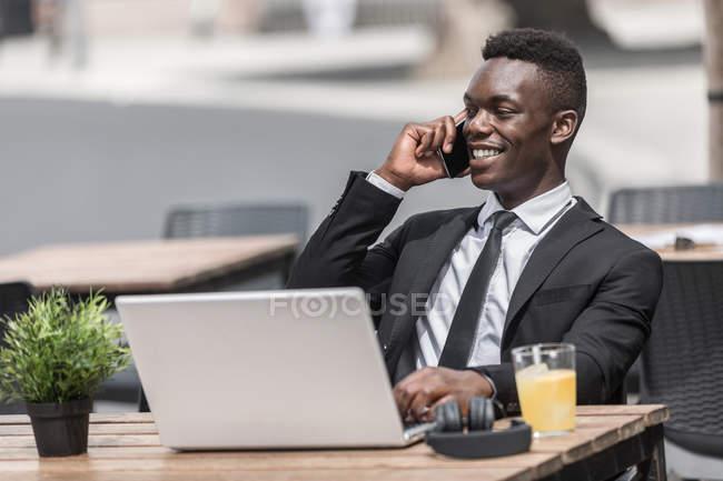 Afro-Américain beau pigiste parlant au téléphone tout en travaillant sur ordinateur portable dans la cafétéria urbaine — Photo de stock