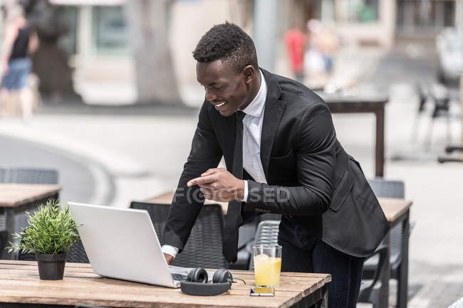 African American smiling freelancer pointing to laptop in urban cafeteria — Stock Photo