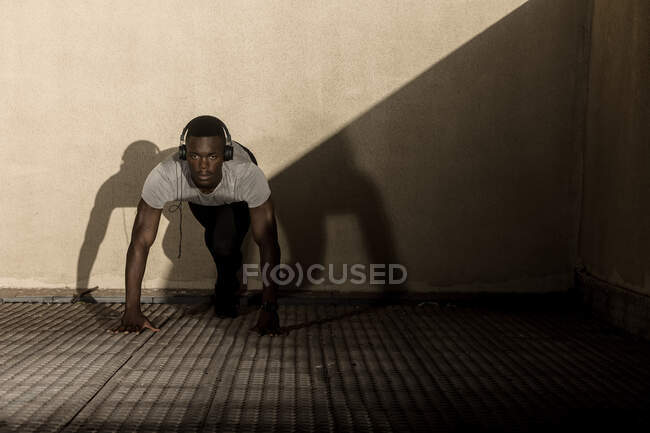 Concentrating adult African American athlete in sportswear and headphones ready to run on walkway against gray wall during daytime — Stock Photo