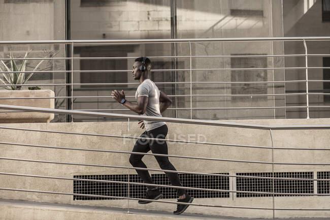 Seitenansicht eines nachdenklichen erwachsenen Afroamerikaners in Sportbekleidung und Kopfhörern, der auf dem Gehweg läuft und an sonnigen Tagen in der Nähe des Gebäudes wegsieht — Stockfoto
