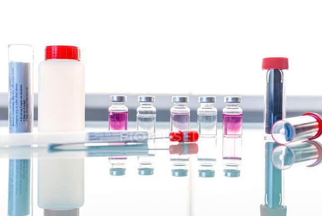 Tubes stériles et échantillons médicaux sur table en verre — Photo de stock