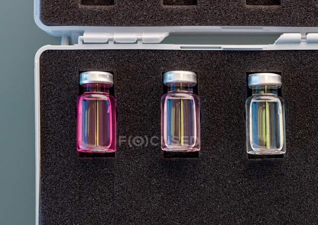 Ampoules en verre fermé ci-dessus avec des échantillons scientifiques disposés dans un boîtier en caoutchouc mousse noire en laboratoire — Photo de stock