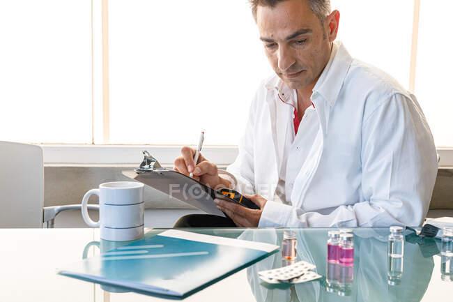 Лабораторний помічник сидить за скляним столом зі зразками та таблетками, які роблять нотатки на дошці та дивляться вниз. — стокове фото