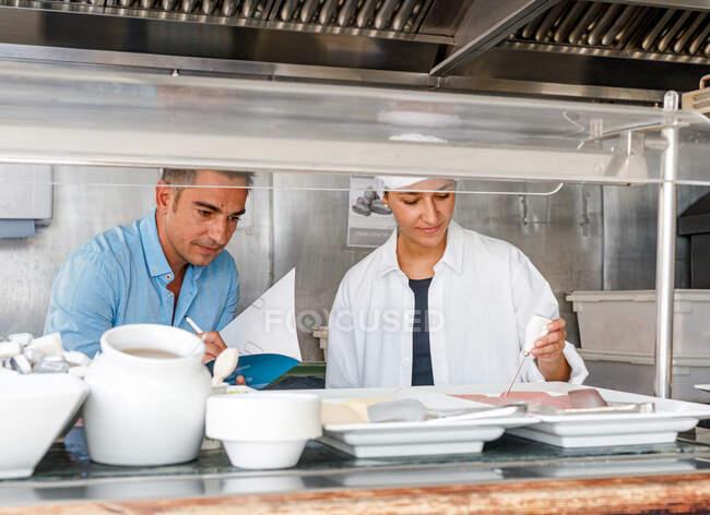 Дорослий старший працівник пише в записниках результати, в той час як доросла жінка-колега в стерильному одязі використовує цифровий пристрій для тестування якості їжі в їдальні — стокове фото