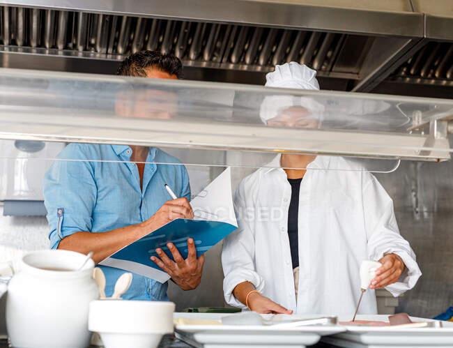 Колеги перевіряють якість їжі в їдальні. — стокове фото