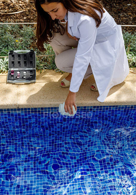 Safety inspector taking water sample from pool — Stock Photo