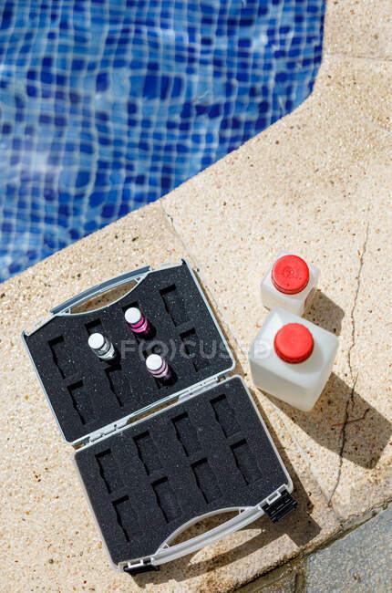 De dessus bouteilles avec des échantillons d'eau et mallette avec des produits chimiques placés près de la piscine lors de l'inspection de sécurité sur place — Photo de stock