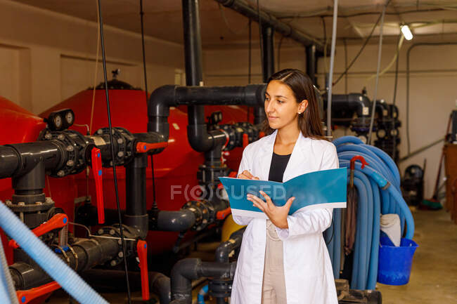 Young female in lab coat checking piping system and writing in journal during safety inspection in industrial facility — Stock Photo