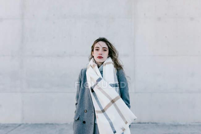 Jeune femme en manteau élégant et écharpe chaude debout contre le mur de construction en béton et regardant à la caméra par temps venteux — Photo de stock