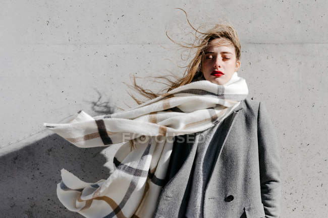 Young woman in stylish coat and warm scarf standing with eyes closed against concrete building wall on windy weather — Stock Photo