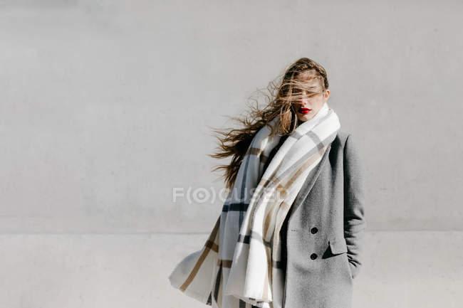 Молода жінка в стильному пальто і теплий шарф стоячи з закритими очима проти бетонних будівельних стін на вітряну погоду — стокове фото