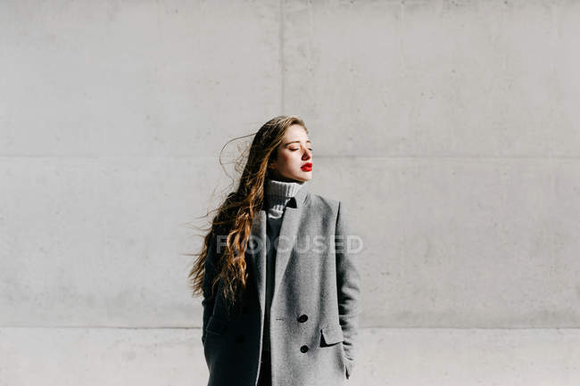 Young woman in stylish grey coat standing with eyes closed against concrete building wall on windy weather — Stock Photo