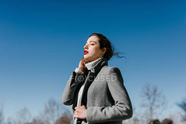 Side view of young female with closed eyes and in stylish gray warm coat standing against clear blue sky on windy weather — Stock Photo