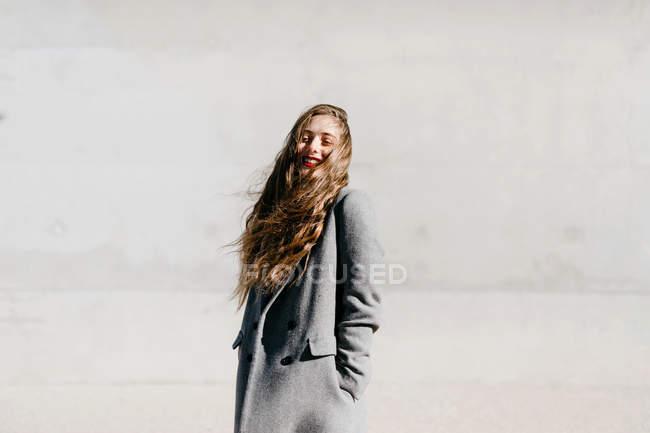 Vue latérale de la femme en manteau élégant debout avec les yeux fermés contre le mur de bâtiment en béton par temps venteux — Photo de stock