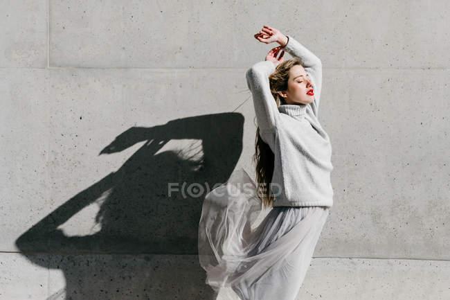 Vue latérale du jeune modèle féminin en pull et jupe élégants avec les yeux fermés et les bras levés contre le mur gris sur la rue de la ville — Photo de stock
