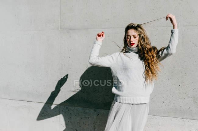 Jeune modèle féminin en pull élégant et jupe avec les yeux fermés touchant les cheveux contre le mur gris sur la rue de la ville — Photo de stock