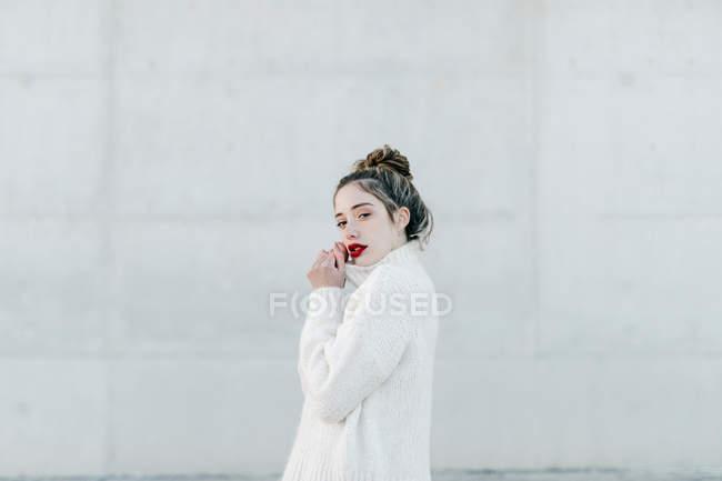 Vue latérale du jeune modèle féminin en chandail chaleureux élégant regardant à la caméra tout en se tenant contre le mur gris sur la rue de la ville — Photo de stock