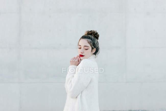 Vue latérale du jeune modèle féminin dans un pull confortable et chaleureux élégant regardant vers le bas tout en se tenant contre un mur gris sur la rue de la ville — Photo de stock