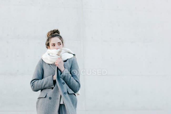 Giovane donna coperta di sciarpa calda guardando lontano mentre in piedi contro muro edificio sulla strada della città — Foto stock