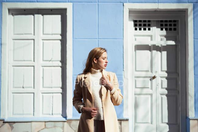 Jeune femme en chemisier élégant regardant loin tout en se tenant près de la porte blanche du bâtiment bleu sur la rue — Photo de stock