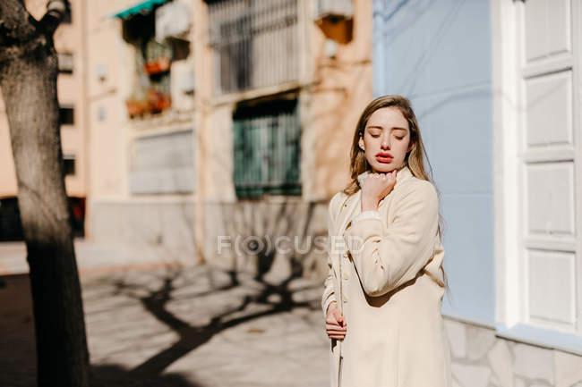 Jeune femme en chemisier élégant avec les yeux fermés debout près du bâtiment sur la rue en arrière-plan flou — Photo de stock