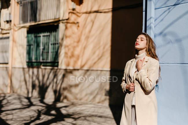 Jeune femme en chemisier élégant avec les yeux fermés debout près du bâtiment bleu sur la rue en arrière-plan flou — Photo de stock
