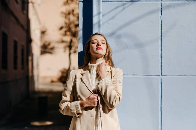 Jeune femme en chemisier élégant avec les yeux fermés tout en se tenant près du bâtiment bleu sur la rue en arrière-plan flou — Photo de stock