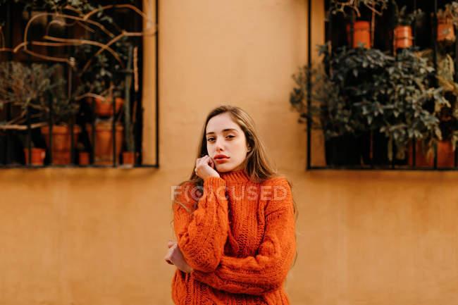 Sensuelle fille en chandail tricoté à la mode touchant le menton et regardant dans la caméra à l'extérieur de la maison avec des plantes en pot sur les fenêtres — Photo de stock