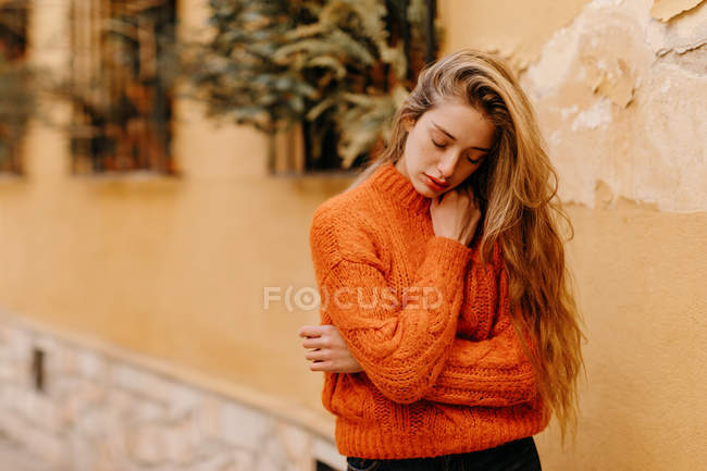 Sensual young female in trendy knitted sweater touching chin with closed eyes house with potted plants — Stock Photo