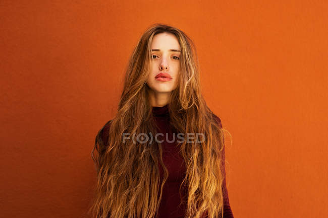 Portrait de jeune femme séduisante aux cheveux longs regardant en caméra contre un mur orange sur la rue — Photo de stock