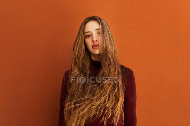 Портрет привлекательной молодой женщины с длинными волосами, глядя в камеру против оранжевой стены на улице — стоковое фото