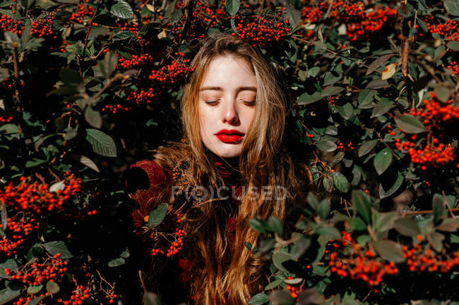 Young female with closed eyes standing amidst green branches with red berries on sunny day in garden — Stock Photo
