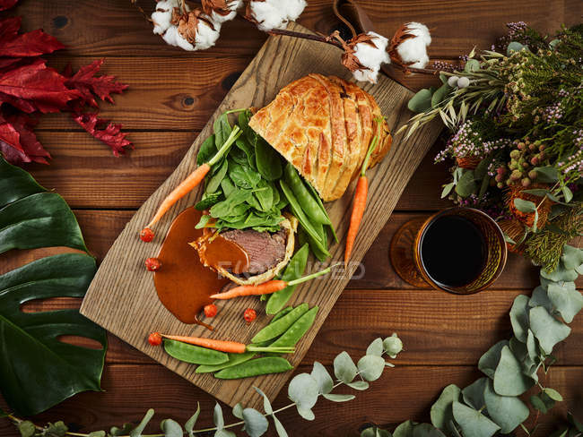 Вид сверху на филе Веллингтона со свежими овощами и красным вином на столешницы пиломатериалов — стоковое фото