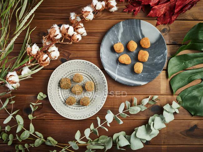 Dall'alto rami e foglie di varie piante disposte intorno a piatti con gustose crocchette sul tavolo in legno — Foto stock